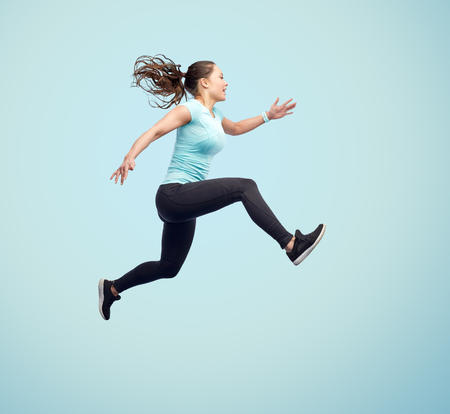 Photo pour sport, fitness, motion and people concept - happy smiling young woman jumping in air over blue background - image libre de droit