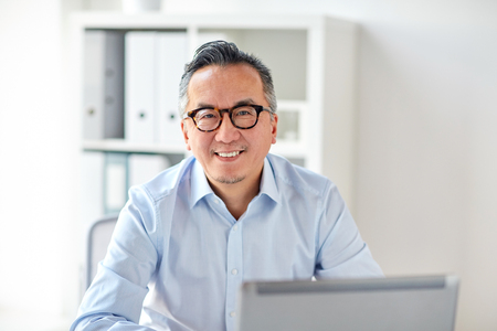 Foto de happy businessman in eyeglasses with laptop office - Imagen libre de derechos
