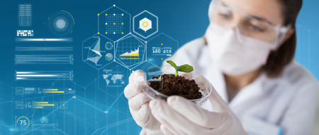 Foto de science, biology, ecology and research concept - close up of young female scientist wearing protective mask holding petri dish with plant and soil sample over blue background and virtual charts - Imagen libre de derechos