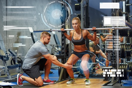 Foto de sport, fitness, teamwork, bodybuilding and people concept - young woman and personal trainer with barbell flexing muscles in gym over virtual charts - Imagen libre de derechos