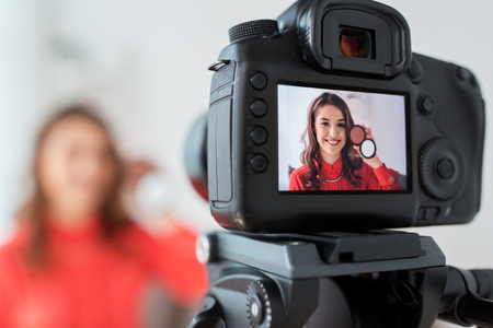 Foto de blogging, technology, videoblog, makeup and people concept - happy smiling woman or beauty blogger with bronzer and camera recording tutorial video at home - Imagen libre de derechos