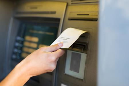 Photo pour close up of hand taking receipt from atm machine - image libre de droit
