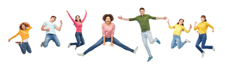 Foto de happiness, freedom, motion and people concept - smiling young international friends jumping in air over white background - Imagen libre de derechos