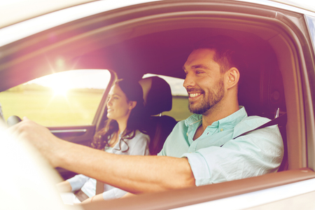 Photo pour leisure, road trip, travel, family and people concept - happy man and woman driving in car - image libre de droit