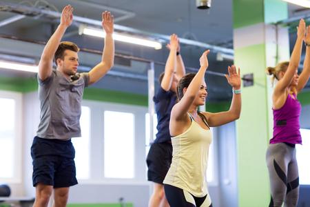 Foto de group of happy friends exercising in gym - Imagen libre de derechos