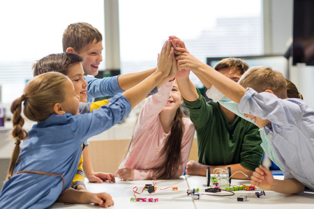 Foto de education, children, technology, science and people concept - group of happy kids building robots and making high five gesture at robotics school - Imagen libre de derechos