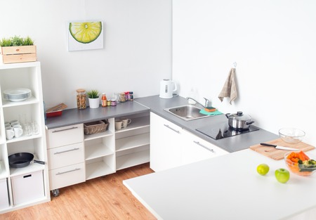 Foto de cooking and interior concept - modern home kitchen with kitchenware, food and spices on table - Imagen libre de derechos