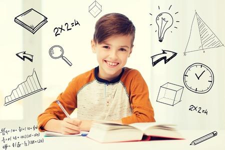 Foto de smiling student boy writing to notebook at home - Imagen libre de derechos