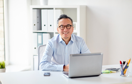Photo for happy businessman in eyeglasses with laptop office - Royalty Free Image