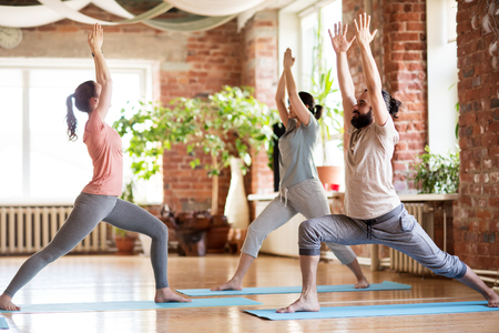 Foto de group of people doing yoga warrior pose at studio - Imagen libre de derechos