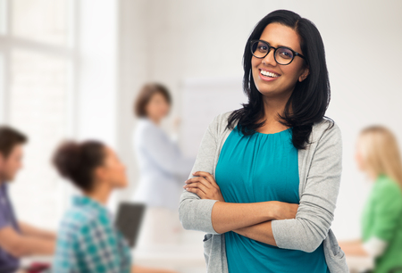 Photo for education, high school and people concept - happy smiling young indian woman or teacher in glasses over classroom background - Royalty Free Image