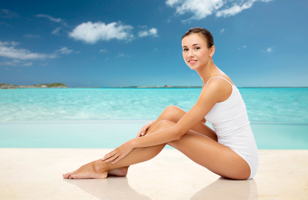 Photo for beautiful woman touching her legs on summer beach - Royalty Free Image