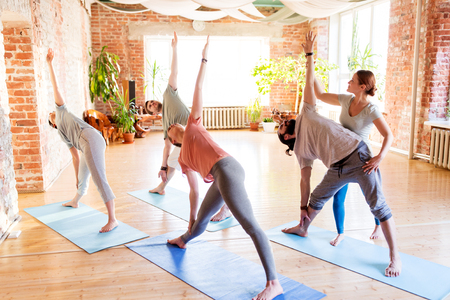 Photo pour fitness, sport and healthy lifestyle concept - group of people with personal trainer doing yoga exercises on mats in gym or studio - image libre de droit
