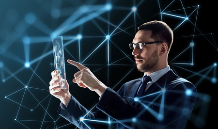 Photo for business, augmented reality and future technology concept - businessman in glasses working with transparent tablet pc computer and virtual low poly shape projection over black background - Royalty Free Image