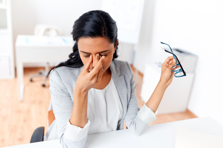 Foto de businesswoman rubbing tired eyes at office - Imagen libre de derechos