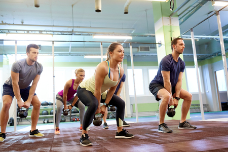 Photo pour sport, fitness, weightlifting and training concept - group of people with kettlebells and heart-rate trackers exercising in gym - image libre de droit