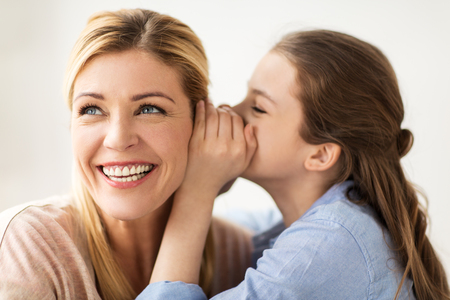 Photo pour people, trust and family concept - happy daughter whispering secret to her mother - image libre de droit