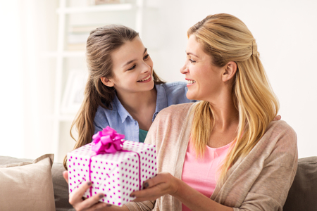 Foto de people, holidays and family concept - happy girl giving birthday present to mother at home - Imagen libre de derechos