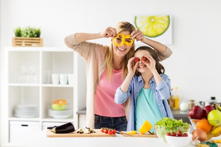 Foto de healthy eating, family and people concept - happy mother and daughter cooking vegetables for dinner and having fun at home kitchen - Imagen libre de derechos