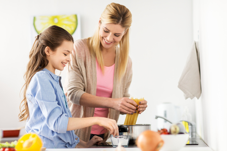 Foto de food, family and people concept - happy mother and daughter cooking and boiling spaghetti pasta for dinner at home kitchen - Imagen libre de derechos