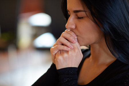 Photo for close up of unhappy woman praying god at funeral - Royalty Free Image