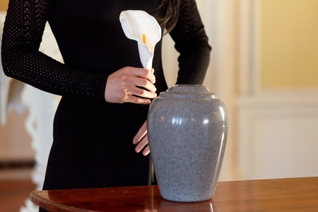 Photo for woman with cremation urn at funeral in church - Royalty Free Image