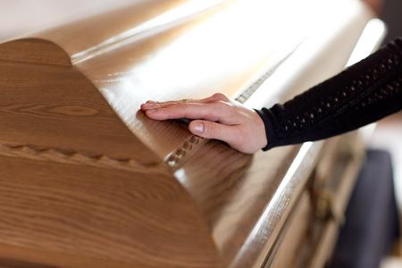 Photo pour woman hand on coffin lid at funeral in church - image libre de droit