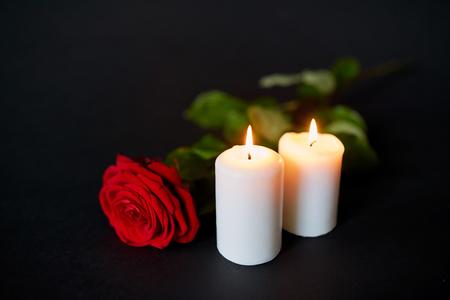 Foto de red rose and burning candles over black background - Imagen libre de derechos