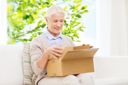 Foto de happy senior woman with parcel box at home - Imagen libre de derechos