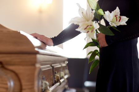 Photo for woman with lily flowers and coffin at funeral - Royalty Free Image