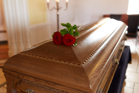 Photo pour red rose flowers on wooden coffin in church - image libre de droit