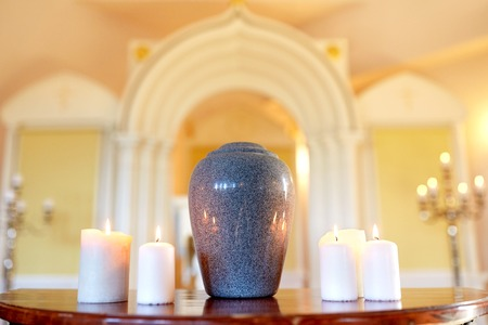 Photo for cremation urn and candles burning in church - Royalty Free Image