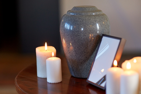 Photo for photo frame, cremation urn and candles on table - Royalty Free Image