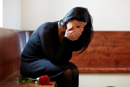 Photo pour crying woman with red rose at funeral in church - image libre de droit