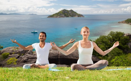 Photo for happy couple doing yoga and meditating outdoors - Royalty Free Image
