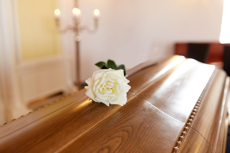 Photo for funeral and mourning concept - white rose flower on wooden coffin in church - Royalty Free Image