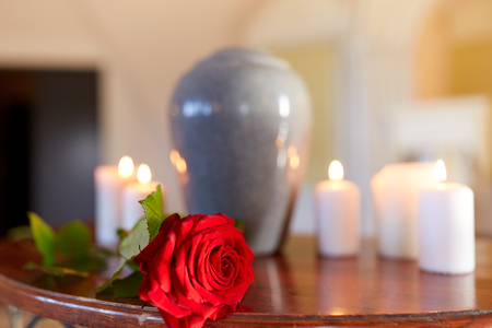Photo pour red rose and cremation urn with burning candles - image libre de droit