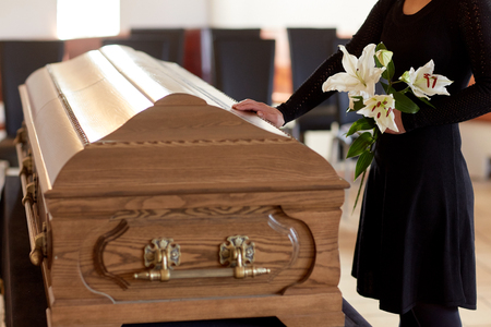 Photo pour woman with lily flowers and coffin at funeral - image libre de droit