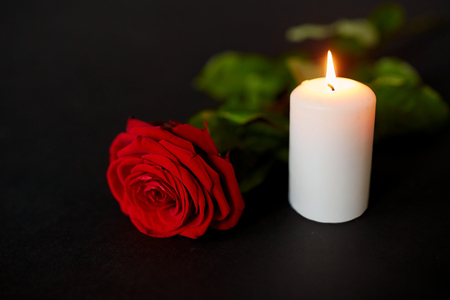 Foto de red rose and burning candle over black background - Imagen libre de derechos