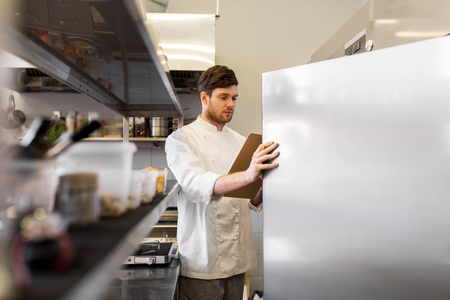Photo pour chef with clipboard doing inventory at kitchen - image libre de droit