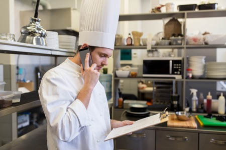 Foto de chef cook calling on smartphone at restaurant kitchen - Imagen libre de derechos