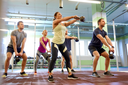 Photo pour group of people with kettlebells exercising in gym - image libre de droit