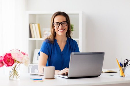 Photo pour happy woman with laptop working at home or office - image libre de droit
