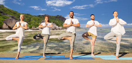 Photo for people making yoga in tree pose on mats outdoors - Royalty Free Image
