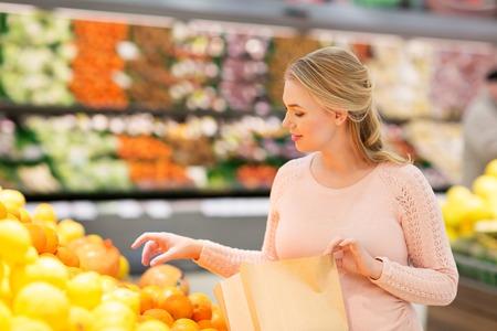 Foto de pregnant woman with bag buying oranges at grocery - Imagen libre de derechos