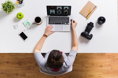 Photo for woman with camera flash drive and laptop at table - Royalty Free Image