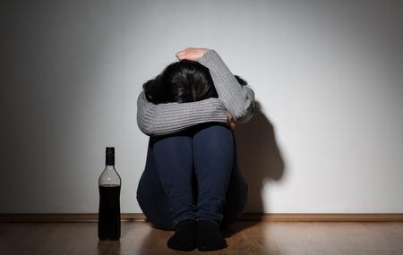 Foto de woman with bottle of alcohol crying at home - Imagen libre de derechos