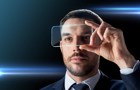 Photo pour business, augmented reality and future technology concept - businessman in suit working with transparent smartphone over black background - image libre de droit