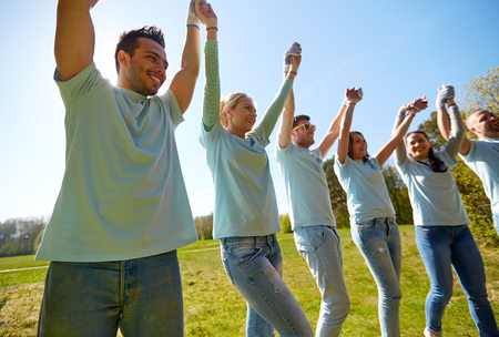 Photo pour volunteering, charity and people concept - group of happy volunteers holding hands outdoors - image libre de droit