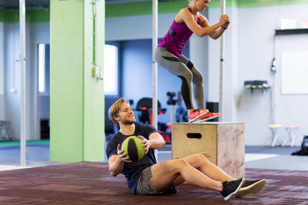 Foto de fitness, sport, training, exercising and people concept - happy woman and man with medicine ball doing curl ups and box jumps in gym - Imagen libre de derechos